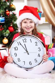 Piękna mała dziewczynka z zegarem w oczekiwaniu na nowy rok w świątecznie urządzonym pokoju