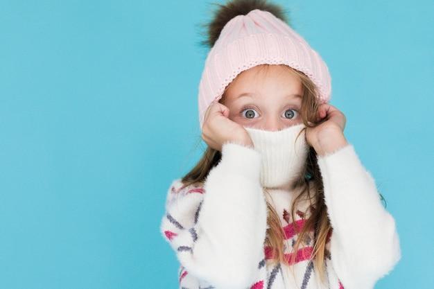 Piękna mała dziewczynka zakrywa jej twarz