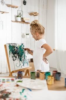Piękna mała europejska dziewczynka o skoncentrowanym spojrzeniu podczas pracy nad swoim zdjęciem w pokoju sztuki.