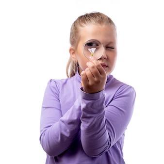 Piękna mała kaukaska dziewczyna o blond włosach wygląda przez szkło powiększające na białym tle