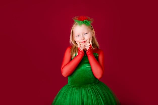 Piękna mała pulchna dziewczynka księżniczka tańczy w luksusowej zielonej sukni na białym tle na czerwonej ścianie. karnawałowa impreza z kostiumami