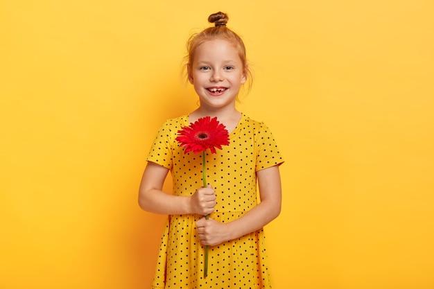Piękna mała rudowłosa dziewczyna pozuje z kwiatem w żółtej sukience