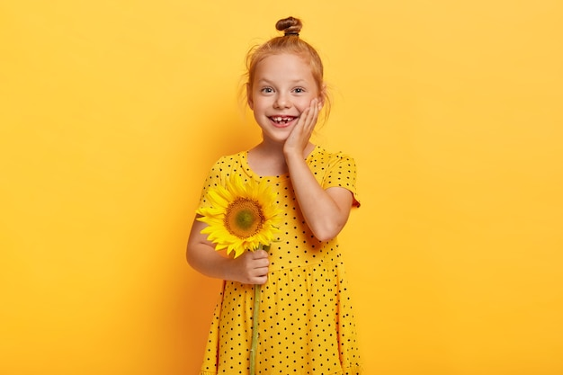 Piękna mała rudowłosa dziewczyna pozuje ze słonecznikiem w żółtej sukience