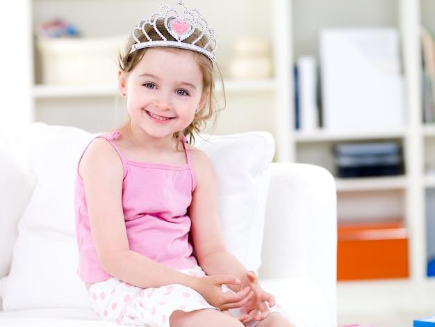 Piękna mała śliczna księżniczka w koronie z uśmiechem siedzi na kanapie