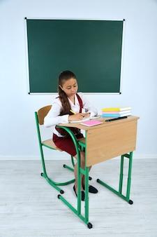 Piękna mała uczennica w klasie w pobliżu tablicy