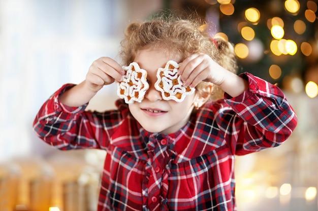 Piękna mała uśmiechnięta dziewczyna trzyma świąteczne ciasteczka na oczach. świąteczny czas na zabawę w domu. słodycze noworoczne
