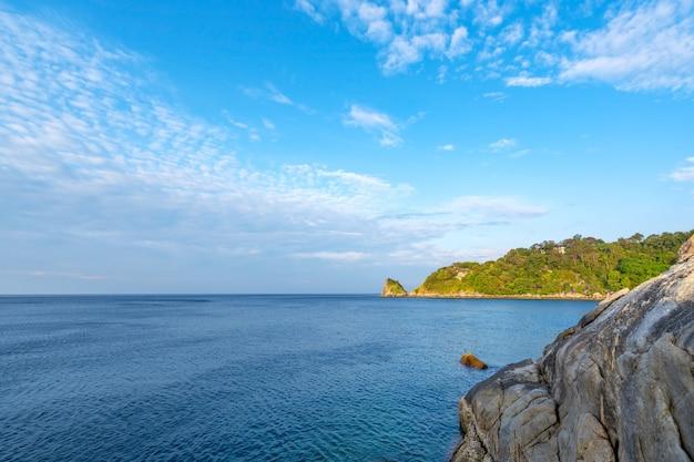 Piękna mała wyspa na morzu naturalny krajobraz pięknej scenerii na wyspie phuket w niebieskim czasie ze skałami na pierwszym planie.
