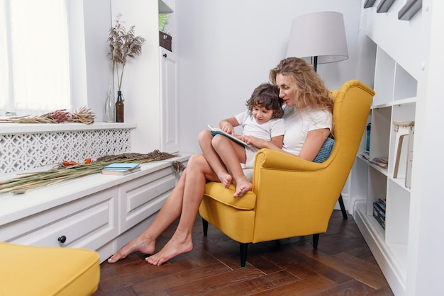 Piękna mama czyta książeczkę dziecięcą swojemu małemu synowi, siedząc w wygodnym żółtym krześle przy oknie w przytulnym domu.