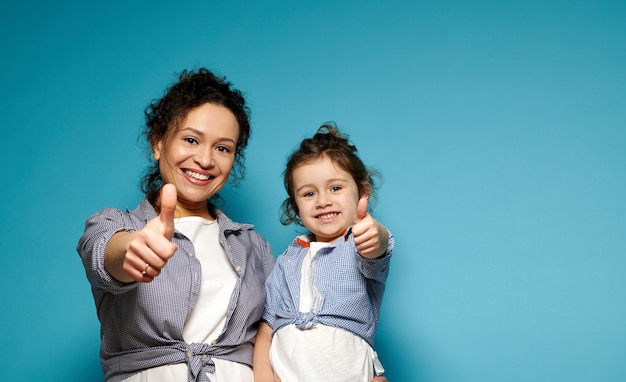 Piękna mama i córka jednakowo ubrane, pokazując kciuki do góry i uroczo uśmiechnięte, pozując do przodu, stojąc na niebieskiej powierzchni z miejscem na kopię