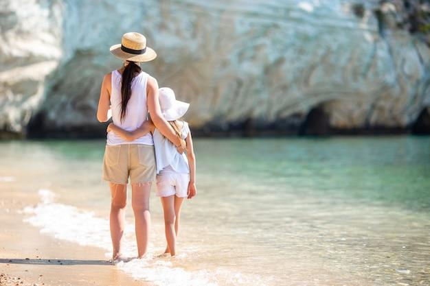 Piękna mama i córka na plaży, ciesząc się wakacjami,