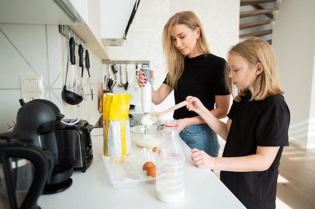 Piękna mama i córka w kuchni zajmują się gotowaniem