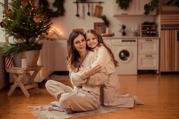 Piękna mama i córka w pobliżu choinki