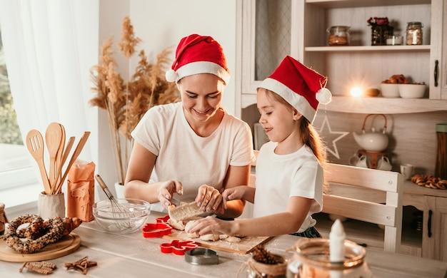 Piękna mama i córka w świątecznych czapkach siedzą przy stole w kuchni i ugniatają ciasto