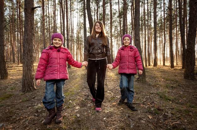Piękna mama i dwie córki spacerujące po słonecznym lesie
