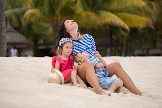 Piękna mama i dwoje dzieci korzystających z wakacji na plaży