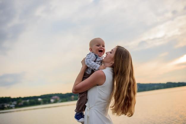 Piękna mama i jej syn bawią się nad jeziorem