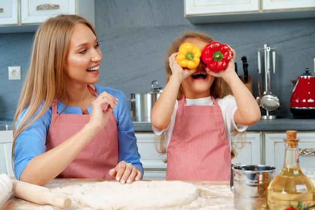 Piękna mama i jej urocza córka bawią się w kuchni podczas gotowania potraw w domu