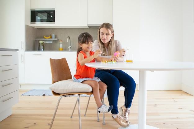 Piękna mama maluje pisankę z córką w kuchni.