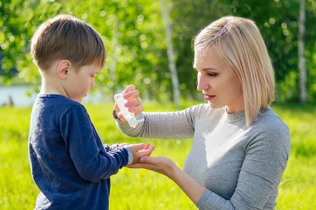 Piękna mama nakłada antyseptyczny żel na uroczą rączkę syna w parku na tle zielonej trawy i drzew
