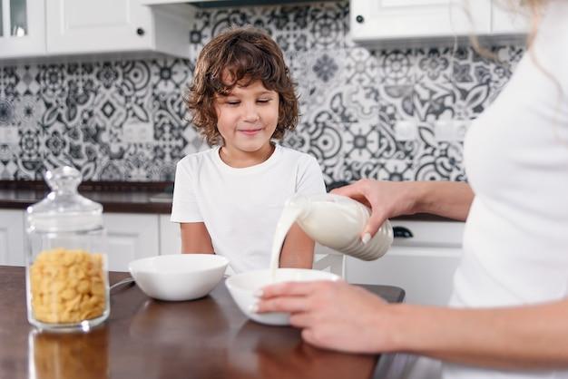 Piękna mama nalewa mleko do talerza ze płatkami. piękna mama przygotowuje śniadanie dla ukochanego syna