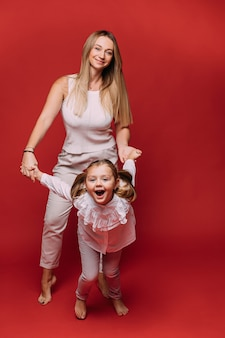 Piękna mama świetnie się bawi ze swoją śliczną córeczką i uśmiechem, obrazek na czerwonym tle