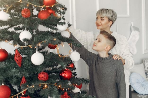 Piękna mama w białym swetrze. rodzina w ozdób choinkowych. mały chłopiec w pokoju