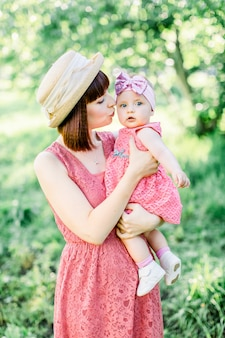 Piękna mama w słomkowym kapeluszu i jej córeczka na zewnątrz wyglądają w różowej sukience. plenerowy portret szczęśliwa rodzina. wygląd rodziny. mama całuje córkę w policzek.