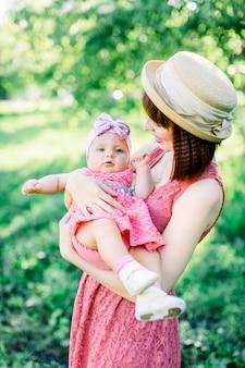 Piękna mama w słomkowym kapeluszu i jej córeczka na zewnątrz wyglądają w różowej sukience. plenerowy portret szczęśliwa rodzina. wygląd rodziny. matka i dziecko w parku portret