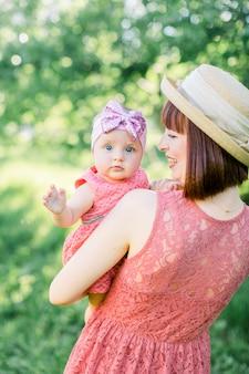 Piękna mama w słomkowym kapeluszu i jej córeczka na zewnątrz wyglądają w różowej sukience. plenerowy portret szczęśliwa rodzina. wygląd rodziny. matka i jej córka w lato parku.