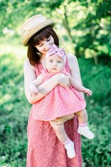 Piękna mama w słomkowym kapeluszu i jej córeczka na zewnątrz wyglądają w różowej sukience. plenerowy portret szczęśliwa rodzina. wygląd rodziny. pozytywne ludzkie emocje, uczucia, emocje.
