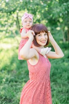 Piękna mama w słomkowym kapeluszu i jej córeczka na zewnątrz wyglądają w różowej sukience. wygląd rodziny. małe dziecko, mała dziewczynka siedzi na ramionach uśmiechniętej mamy