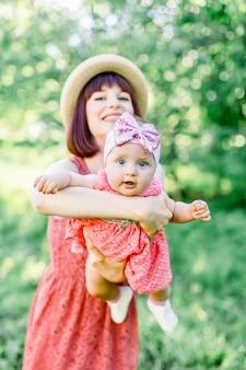 Piękna mama w słomkowym kapeluszu i jej córeczka na zewnątrz wyglądają w różowej sukience. wygląd rodziny. młoda matka rzuca dziecko na niebie, w słoneczny dzień.