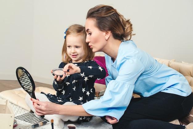 Piękna mama z córeczką robi makijaż w domu. młoda matka i urocza dziewczynka bawią się razem w domu. szczęśliwa rodzina