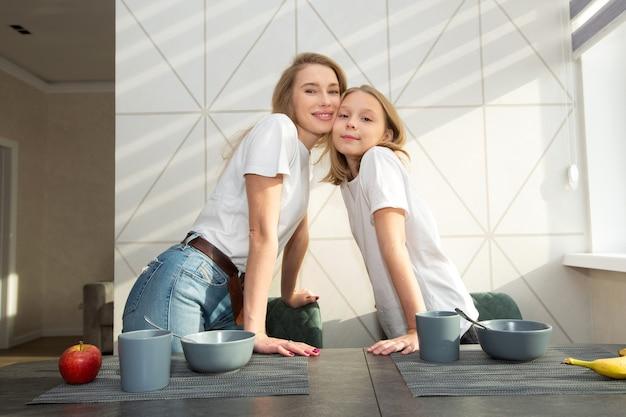 Piękna mama z córką w kuchni w domu przy stole