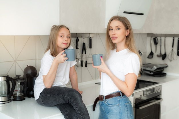 Piękna mama z córką w kuchni z kubkami