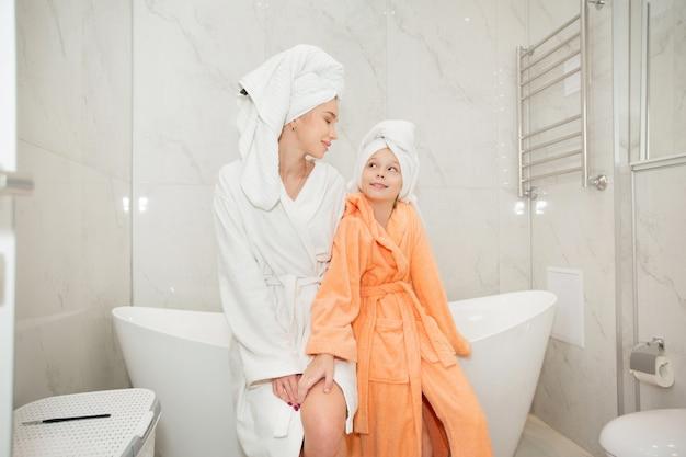 Piękna mama z córką w szlafrokach w łazience