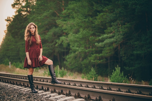 Piękna marzycielska dziewczyna z kręconymi naturalnymi włosami cieszy się przyrodą w lesie na kolei.