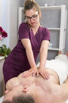 Piękna masażystka wykonuje rewitalizujący masaż klatki piersiowej mężczyźnie. zabieg wellness w spa. relaksujący zabieg spa