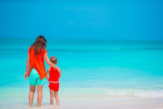 Piękna matka i córka na karaibskiej plaży, ciesząc się wakacjami.