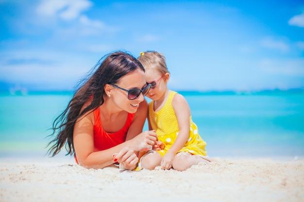 Piękna matka i córka na plaży, ciesząc się wakacjami