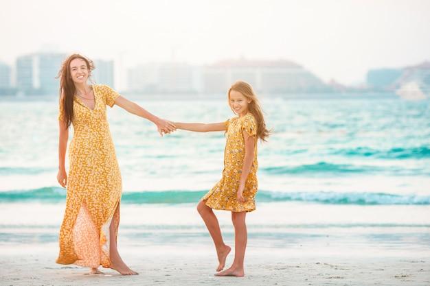 Piękna matka i córka przy plażą cieszy się wakacje.