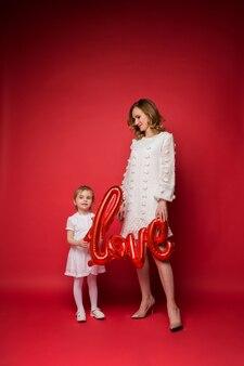 Piękna matka i córka stoją trzymając balon z napisem miłość na czerwono