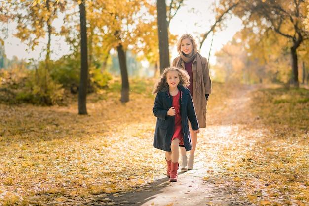 Piękna matka i córka w kolorowej jesieni outdoors