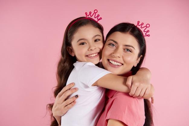 Piękna matka i córka w pozornych koronach obejmujemy.