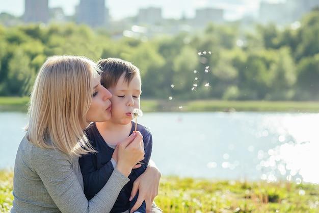 Piękna matka i jej śliczny synek dmuchają balon mniszka lekarskiego w parku na tle zielonej trawy, drzew i jeziora. pojęcie rodzinnych wakacji w przyrodzie.