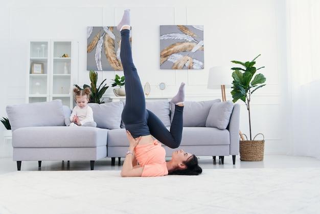 Piękna matka robi poranne ćwiczenia rozciągające, podczas gdy jej córka bawi się