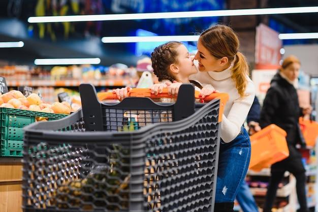 Piękna matka trzyma koszyk z dzieckiem, spacery w supermarkecie