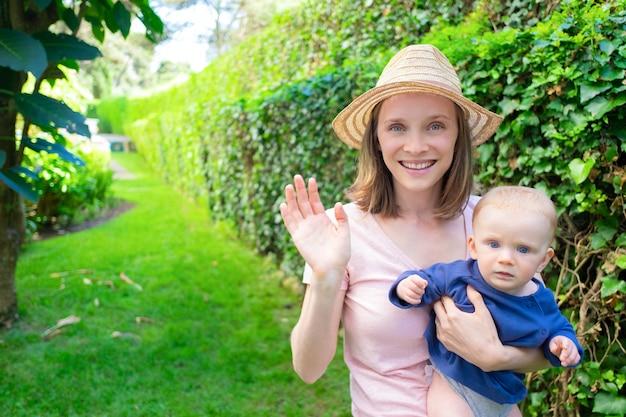 Piękna matka w kapeluszu macha, trzymając noworodka, uśmiechając się i patrząc na kamery. urocze dziecko na rękach mamy, patrząc poważnie. letni czas z rodziną, ogród