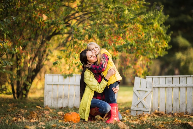 Piękna matka w żółtym płaszczu przeciwdeszczowym przytula swoją córkę w jesiennym parku