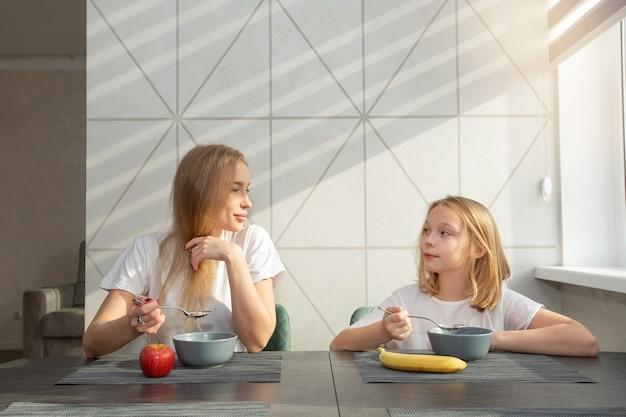 Piękna matka z córką w kuchni w domu przy stole, jedzenie owsianki